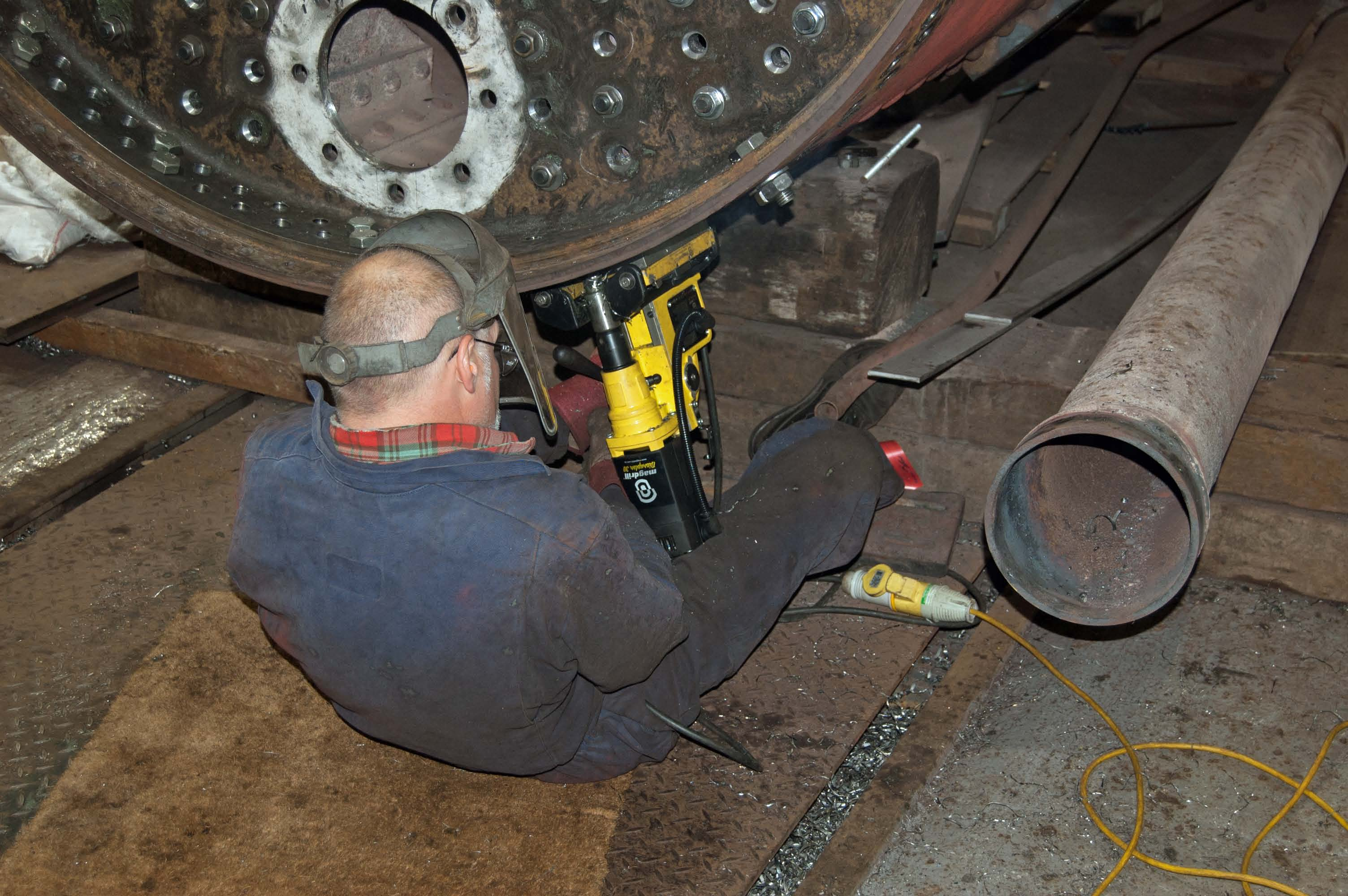 The new front tubeplate is in position, and the holes for the rivets are being drilled.